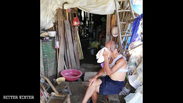 Un ottantenne seduto fuori della sua capanna