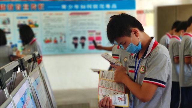 Uno studente legge del materiale propagandistico anti-xie jiao