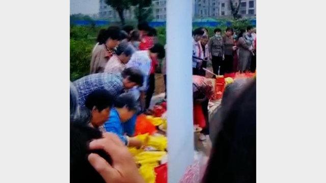 La gente brucia incenso e banconote davanti alla statua di Mao Zedong